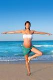 Yoga precticing de la mujer embarazada en playa azul Imágenes de archivo libres de regalías