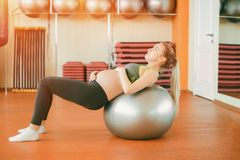 Yoga for pregnant women. Young beautiful pregnant girl in sportswear doing yoga and stroking her belly. Yoga for pregnant women. Young beautiful pregnant girl in stock photography