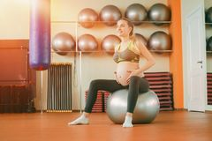 Yoga for pregnant women. Young beautiful pregnant girl in sportswear doing yoga and stroking her belly. Yoga for pregnant women. Young beautiful pregnant girl in stock photos