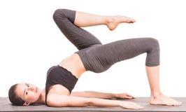 Yoga. Pretty brunette is exercising yoga on white background Royalty Free Stock Photo