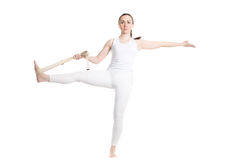 Yoga with props, Extended Hand-To-Big-Toe pose. Sporty beautiful young beginning yoga female student in white sportswear standing in Utthita Hasta stock photography
