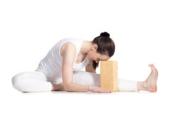 Yoga with props, Head to Knee forward bend yoga asana. Sporty beautiful young beginning yoga student in white sportswear sitting in head to knee forward bend Royalty Free Stock Photo