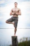 Yoga que hace adulta joven en un tocón en naturaleza Fotos de archivo libres de regalías