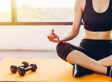 Yoga que se sienta de la mujer hermosa en las manos después del entrenamiento del ejercicio fotografía de archivo