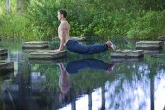 Yoga - équipez et sa réflexion dans l'eau Images libres de droits