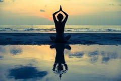 yoga Ragazza che fa meditazione vicino alla spiaggia dell'oceano Immagine Stock