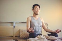 Yoga relajante del hombre joven en cama después de despertar por la mañana imagen de archivo libre de regalías
