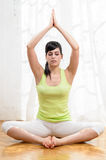 Yoga and Relax. Beautiful young woman doing yoga exercise and meditating at home Stock Images