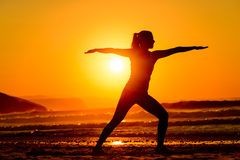 Yoga and relax on beach  at sunset. Yoga exercises in beach on beautiful summer sunset alone. Fit female silhouette relaxing, breathing and exercising Royalty Free Stock Image