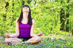 Yoga relaxation in forest. Young woman in lotus pose at the meditation in forest stock image