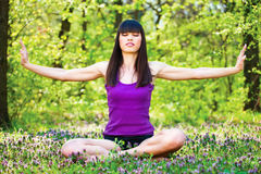Yoga relaxation in forest. Young woman doing meditation outdoor in forest stock photos