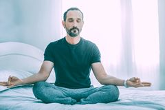 Relaxed concentrated man meditating in a room stock images