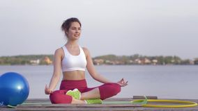 Yoga relaxing, young attractive yogi girl in lotus position meditates and delight spiritual calmnes on nature. Near river stock video footage
