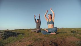 Yoga religion, sports pair together meditating in lotus position on meadow on background of sky. Yoga religion, sports pair together meditating in lotus position stock video