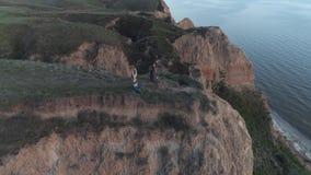 Yoga Religion, Yogi Mann und Frau in Lotus Position meditat in der Natur sitzen auf Klippe nahe Meer stock footage