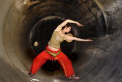 Yoga Revolve. Woman in yoga pose inside a large cylindrical interior Stock Photo