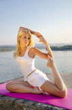 Yoga by the river pigeon pose Stock Image