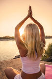Yoga by the river at sunset Stock Photo
