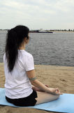 Yoga river. Woman sitting in lotus position on a river bank, half back view Stock Photography