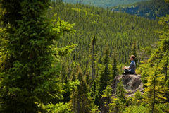 Young man on a rock in the middle of the nature Stock Photography