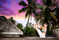 Yoga on the roof in India. Yoga naukasana boat pose by woman in white cloth on the roof at palm trees and sunset background in Varkala, Kerala, India Stock Photo