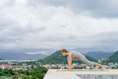 Yoga on rooftop. Happy young woman stretching on roof with city and mountains view Stock Image