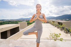 Yoga on he rooftop. Practicing yoga in the morning, with city and mountains view. Attractive young caucasian woman standing in yoga pose on the roof Stock Photography