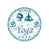 Yoga rubber stamp. Blue grunge rubber stamp with two people silhouettes practicing yoga and the word Yoga written inside the stamp Stock Image