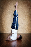 Yoga salamba sarvangasana shoulder stand pose. Handsome Indian man in white shirt doing salamba sarvangasana, shoulder stand inverted pose indoors on wooden stock photos