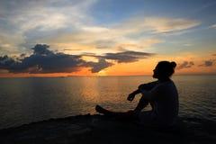 Yoga scene silhouette in sunset. Stock Photo