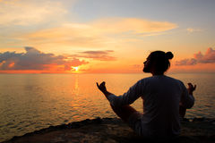 Yoga scene silhouette in sunset. Stock Image
