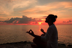 Yoga scene silhouette in sunset. Royalty Free Stock Images