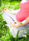 Yoga, schöne schwangere Frau, die im Park sich entspannt Lizenzfreies Stockfoto