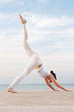 Yoga at sea. Young beautiful woman doing yoga excercise outdoor at sea: Parvatasana pose Royalty Free Stock Image