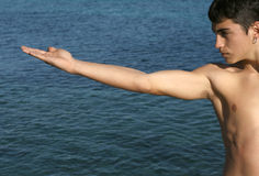 Yoga by the sea. Young man doing yoga moves by the sea Royalty Free Stock Images