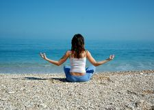 Yoga and sea. A young beautiful girl doing yoga in front of the adriatic sea royalty free stock images