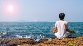 Yoga at the sea. Asian man having yoga beside the sea Stock Image