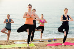 Yoga on sea beach, group of young women. Practicing position royalty free stock photography