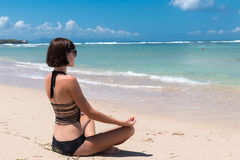 Yoga in the sea or ocean beach. Girl meditating in lotus pose on the tropical island Bali, Indonesia.. Healthy lifestyle Stock Photos