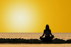 Yoga by the sea. Picture of a woman doing yoga in the early morning Royalty Free Stock Images