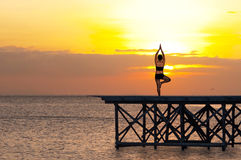 Yoga by the sea. Picture of a woman doing yoga in the early morning Royalty Free Stock Image