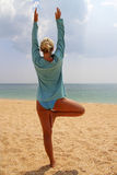 Yoga at the seashore. Woman doing exercises at the seashore Stock Image
