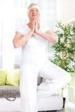 Yoga senior sorridente di esercizio della donna a casa Fotografia Stock