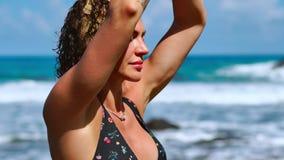 Yoga serena de la meditación Mujer turística morena que medita en la posición de loto respecto al promontorio sobre el Praia escé almacen de video