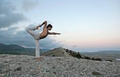 Yoga series. Young man doing yoga on the mountain Royalty Free Stock Image