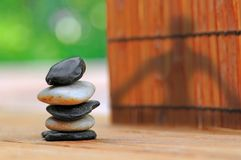 Yoga Shadow by Stacked Stones in Garden Stock Image