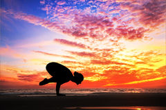 Yoga silhouette on the beach. Yoga bakasana crane pose by woman in silhouette with dramatic sunset sky background. Free space for text Stock Image