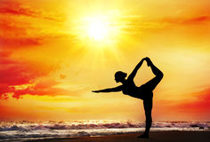 Yoga silhouette on the beach. Yoga natarajasana dancer pose by woman in silhouette with dramatic sunset sky background. Free space for text Stock Photos