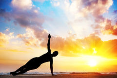Yoga silhouette on the beach. Yoga vasisthasana, side plank pose by woman in silhouette with sunset sky background. Free space for text Royalty Free Stock Photography