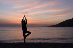 Yoga silhouette on the beach at sunset. Male yoga silhouette on the beach at sunset royalty free stock photography